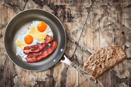 fryingpan: Fried Eggs and Pork Bacon Rashers in Teflon Frying Pan with slice of Integral Bread on Old Cracked Peeled Wooden Table Stock Photo