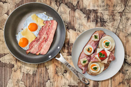 teflon: Fried Eggs and Pork Bacon Rashers in Teflon Frying Pan with Plate of Bacon, Cheese, Egg, Ham, and Tomato Sandwich on Old Cracked Peeled Wooden Garden Table