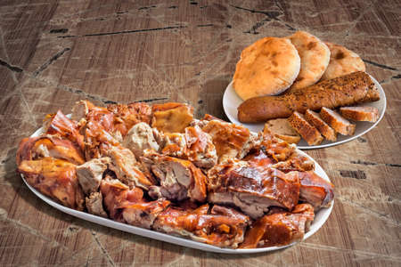 peeledoff: Plateful of Spit Roasted Pork with Baguette Brown Integral Bread Cut In Slices and Three Pita Bread Loafs Set on Old Cracked Peeled Wooden Garden Table