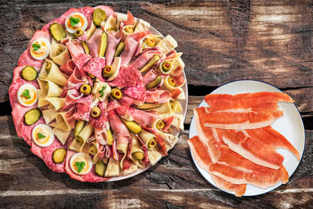 plateful: Plateful of Appetizer Meze with Smoked Pork Ham Prosciutto on Old Wooden Picnic Table