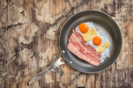 peeledoff: Fried Eggs and Pork Bacon Rashers in Teflon Frying Pan on Old Cracked Peeled Wooden Garden Table