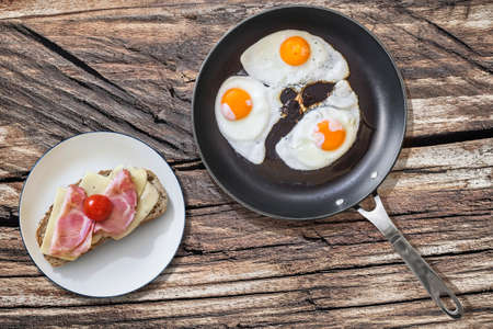 fryingpan: Fried Eggs in Teflon Frying Pan with Bacon Rashers and Tomato Sandwich on Old Wooden Picnic Table