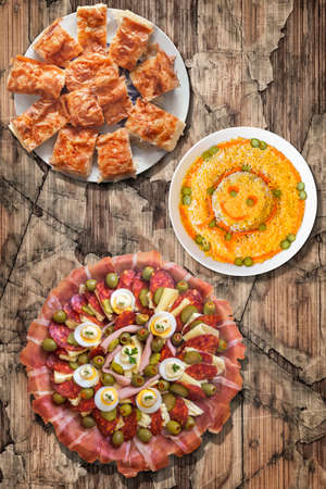 plateful: Plateful of Serbian Traditional Appetizer Meze with Gibanica Crumpled Cheese Pie and Garnished Olivier Salad Set on Old Cracked Wood Surface Stock Photo