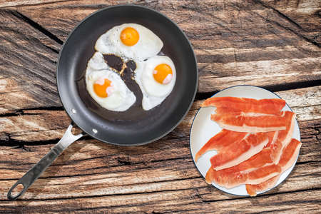 teflon: Fried Eggs in Teflon Frying Pan with Plateful of Prosciutto Ham Slices on Old Picnic Wooden Table Stock Photo