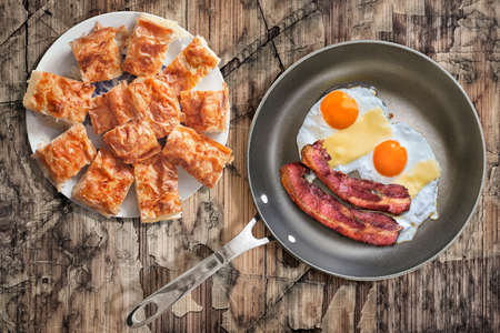 teflon: Fried Eggs and Pork Bacon Rashers in Teflon Frying Pan with Plateful of Serbian Gibanica Cheese Crumpled Pie on Old Cracked Peeled Wooden Table Stock Photo