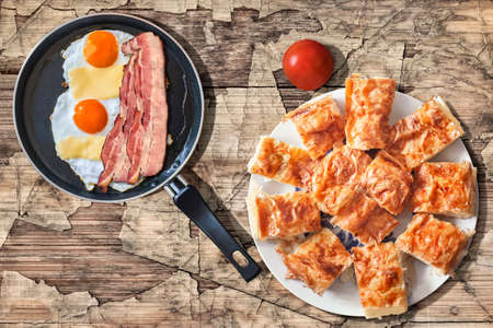 peeledoff: Fried Eggs and Bacon Rashers in Teflon Frying Pan with Tomato and Plateful of Gibanica Cheese Pie Slices Set on Old Cracked Wood Surface