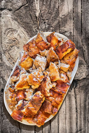 peeledoff: Plateful of Spit Roasted Pork Slices on Old Lacquered Cracked Peeled-off Wooden Garden Table