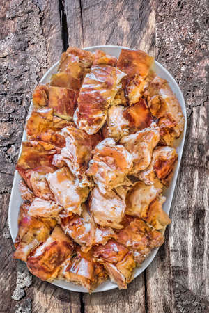 to spit: Plateful of Spit Roasted Pork Slices on Old Wooden Picnic Table
