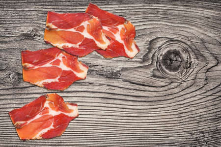 Dry Cured Pork Neck Slices On Old Knotted Wooden Picnic Table