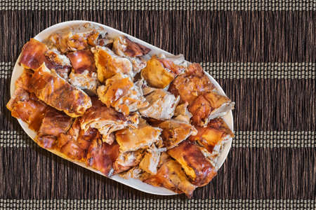 Plateful of Spit Roasted Pork Slices On Paper Parchment Woven Place Mat