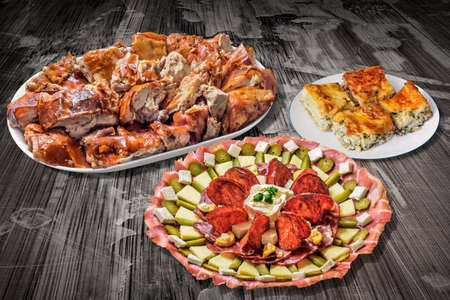 peeledoff: Appetizer Dish Meze With Plateful of Spit Roasted Pork And Cheese Pie Slices On Old Cracked Flaky Wooden Garden Table