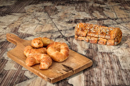peeledoff: Bunch Of Sesame Puff Pastry On Old Cutting Board And Integral Bread Loaf Set On Cracked Flaky Wooden Grunge Background Stock Photo