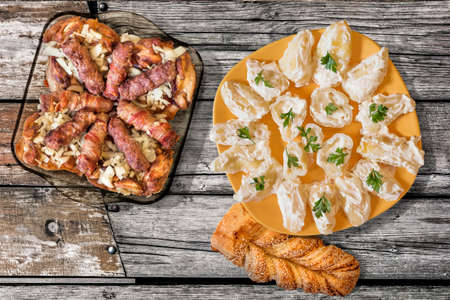 floorboards: Grilled Minced Meat Loafs Cevapcici And Chicken Thighs Dish With Plateful Of Bell Peppers In Sour Cream And Sesame Braid Croissant Set On Old Floorboards Stock Photo