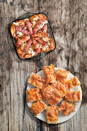 Plateful Of Grilled Minced Meat Loafs Cevapcici Rolled In Bacon With Chicken Meat And Gibanica Crumpled Cheese Pie Set On Old Knotted Cracked Wood Stock Photo