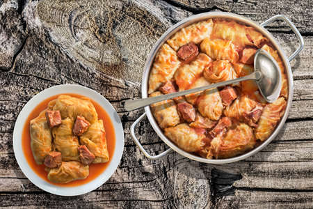 Plateful Of Cabbage Rolls Stuffed With Minced Meat Cooked In Tomato Sauce In Stainless Steel Saucepot Set On Old Wooden Garden Table