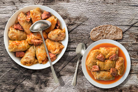 Plateful Of Cabbage Rolls Stuffed With Minced Meat Cooked In Tomato Sauce Served With Some Bread On Old Knotted Wooden Garden Table