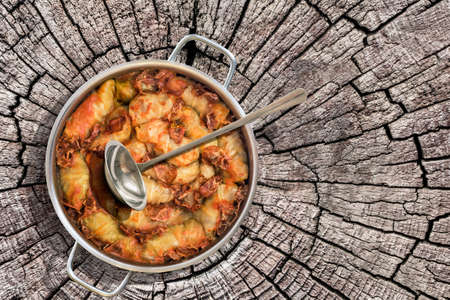 stockpot: Cabbage Rolls Stuffed With Minced Meat Cooked In Tomato Sauce With Smoked Ham Slices In Stainless Steel Saucepot Set On Old Cracked Stump