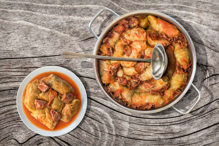 stockpot: Plateful Of Cabbage Rolls Stuffed With Minced Meat Cooked In Tomato Sauce With Smoked Ham Slices In Stainless Steel Saucepot Set On Old Cracked Wood