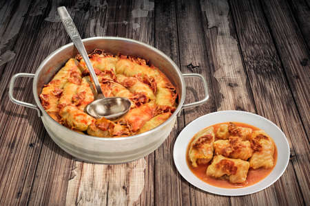 stockpot: Plateful Of Cabbage Rolls Stuffed With Minced Meat Cooked In Tomato Sauce With Smoked Ham Slices In Stainless Steel Saucepot Set On Old Cracked Flaky Garden Table Stock Photo