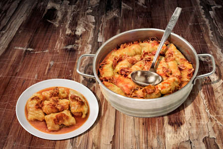 Plateful Of Cabbage Rolls Stuffed With Minced Meat Cooked In Tomato Sauce With Smoked Ham Slices In Stainless Steel Saucepot Set On Old Cracked Flaky Garden Table Stock Photo