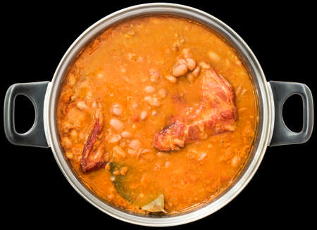 stockpot: Beans Baked With Smoked Pork Ribs In Old Stainless Steel Saucepot Isolated On Black Background