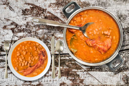 Baked Beans With Smoked Pork Ribs Dinner Served On Old Cracked Wooden Garden Table Stock Photo