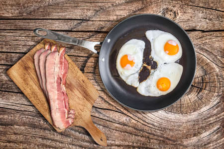 calorie rich food: Sunny Side Up Fried Eggs In Heavy Duty Teflon Frying Pan With Pork Bacon Rashers On Cutting Board Set On Old Cracked Wooden Picnic Table