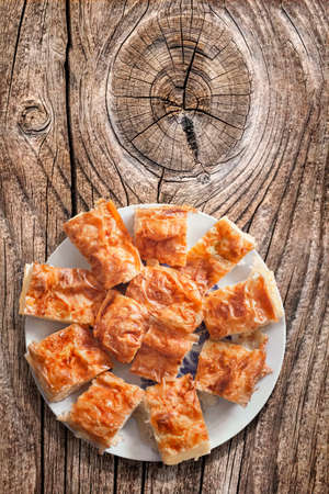 calorie rich food: Plateful Of Serbian Traditional Crumpled Cheese Pie Slices Set On Old Wooden Knotted Cracked Picnic Table
