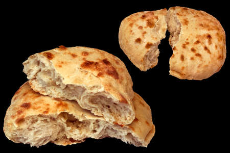 Two Pitta Bread Loafs Torn In Half Isolated On Black Background