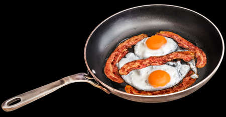 Pair of Sunny Side Up Eggs Fried with Four Bacon Rashers in Old Heavy Duty Steel Frying Pan Isolated on Black Background