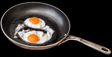 sunny side: Pair of Sunny Side Up Fried Eggs In Old Heavy Duty Steel Frying Pan Isolated On Black Background