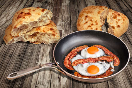 on duty: Sunny Side Up Eggs Fried with Bacon Rashers in Old Frying Pan Set on Weathered Garden Table With Two Torn Pitta Bread Loafs Stock Photo