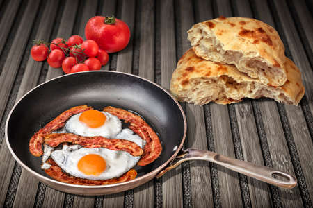 Sunny Side Up Eggs Fried with Four Bacon Rashers in Old Steel Frying Pan Set on Weathered Garden Table With Torn Pitta Bread and Bunch of Fresh Ripe Tomatoes