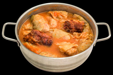Cabbage Rolls Stuffed With Minced Meat Cooked With Smoked Pork Ribs in Stainless Steel Saucepot Isolated On Black Background