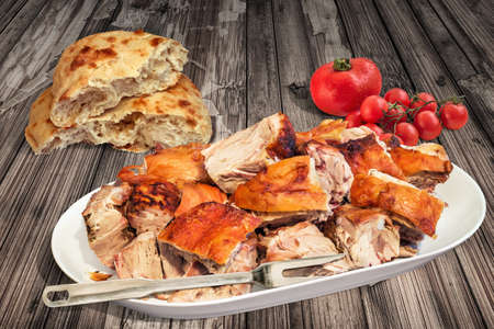 ロースト ポーク肩スライス添え Pitta のパンとトマト古い漆塗りのひびの入った木製ガーデン テーブルの上の束を吐き出す