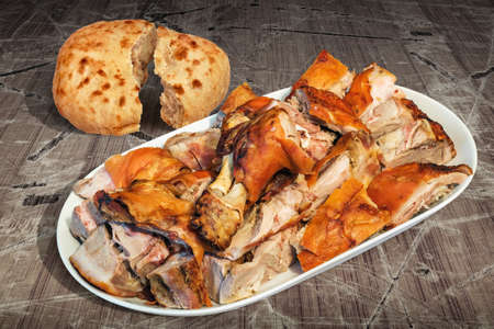 to spit: Spit Roasted Pork Shoulder Slices Served with Pitta Bread on Old Lacquered Cracked Wooden Garden Table