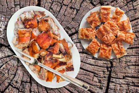 Plateful of Spit Roasted Pork Shoulder Slices and Serbian Crumpled Cheese Pie Gibanica Set on Old Cracked Rustic Stump Picnic Table
