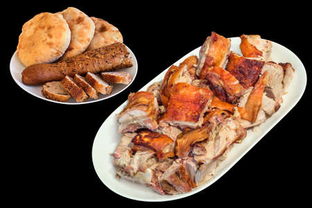 Plateful of Spit Roasted Pork Slices with Cut Integral Baguette and Pitta Bread Loaves Isolated on Black Background
