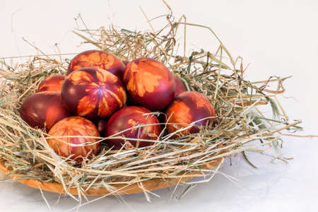 A Bunch of Colorful Easter Eggs, Onion Skin Dyed and Decorated with Leaves Imprints, Laid in Hay Nest, Set on White Background Stock Photo