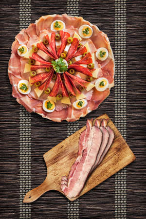 serbian: Appetizer Savory Dish Meze with Bacon Rashers on Wooden Cutting Board Set on Parchment Table Mat