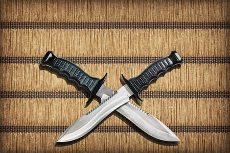 grooves: Two Crossed Blades Tactical Combat Hunting Survival Sawback Bowie Knives Set On Yellow Plaited Paper Parchment Place Mat Vignetted Grunge Texture Stock Photo