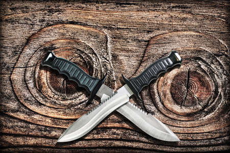 Tactical Combat Hunting Survival Bowie Knives With Crossed Blades On Grunge Vignetted Old Knotted Pinewood Grunge Background