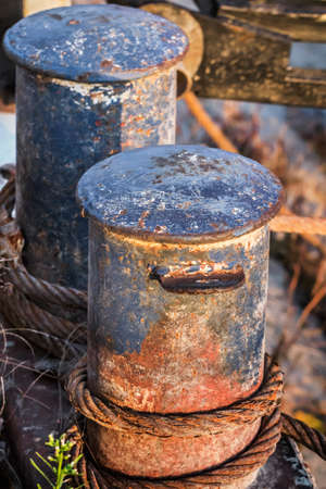 Old Battered Rusty Iron Bollards With Coiled Corroded Steel Cable