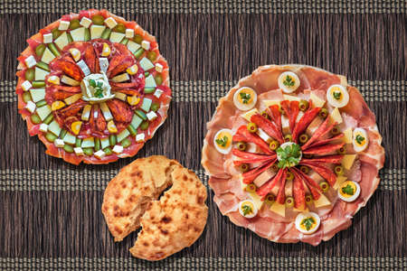 Two Traditional Serbian Welcome Appetizer Savory Dishes Meze And Leavened Pitta Flatbread Torn Loaf Set On Dark Brown Interlaced Plaited Paper Parchment Place Mat