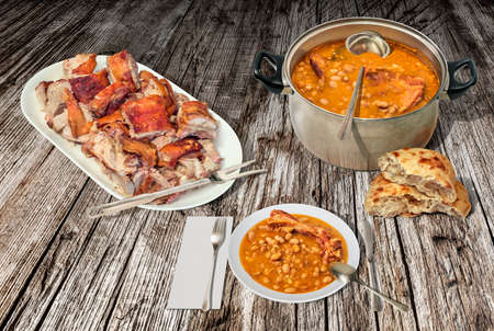 Plateful Of Spit Roasted Pork Meat Chunks Served with Baked Beans and Domestic Pita Leavened Flatbread on Old Weathered Rustic Pinewood Table