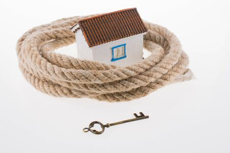 key to freedom: key and a house surrounded by rope