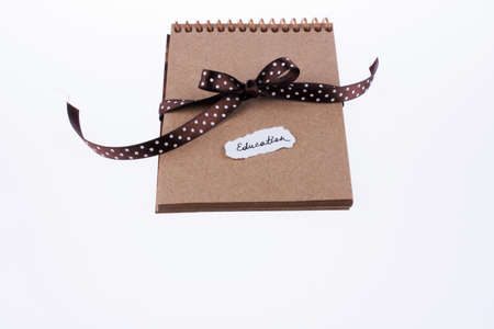 spiral notebook: Spiral notebook with a ribbon and education note on white background