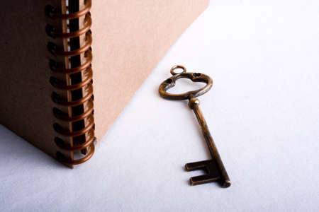 conceptional: key by the side of a  spiral notebook on a white background