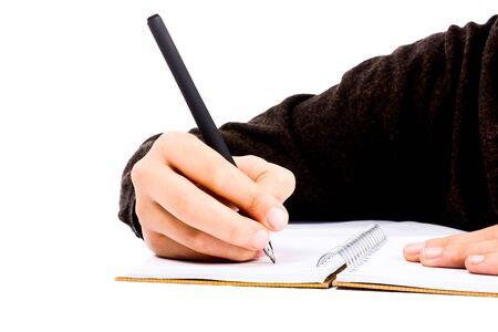 assignments: A child hand is writing with pen on a spiral notebook on white background Stock Photo