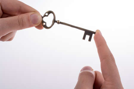 conceptional: hand holding a  retro styled metal key  on a white background